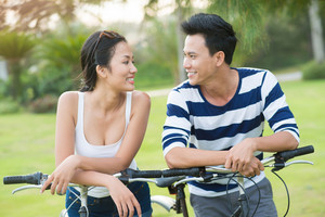 Young couple on bicycles smiling and looking at each other