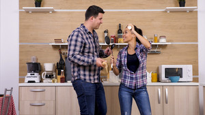 Young couple playing with kitchen tools while dinner get's ready. Funny moment.
