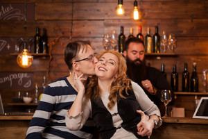 Young couple sitting at bar counter and showing affection. Having fun in pub.