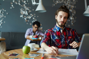 Young creative bearded businessman wearing long hair and colorful casual shirt looking confidently at camera while working with laptop at table in cafe, other people in background