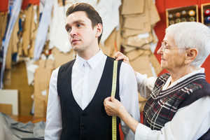 Young customer in shirt and waistcoat visiting tailoring shop