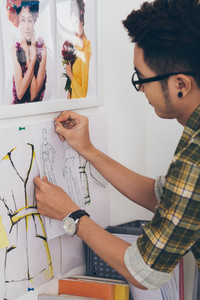 Young designer pinning fashion sketches to the wall