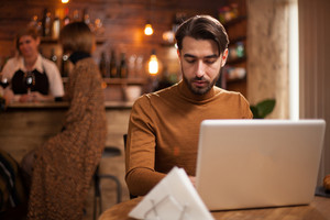 Young entrepreneur working on his laptop in a coffee shop. Attractive businessman. Businessman lifestyle.