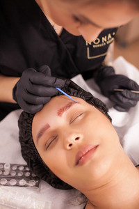 Young female beautician applying skin treatment after the procedure of eyebrow tattoo removal. Female patient. Modern treatment. Body treatment.
