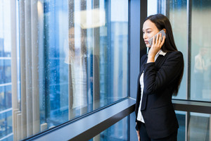 Young female broker consulting client on the phone
