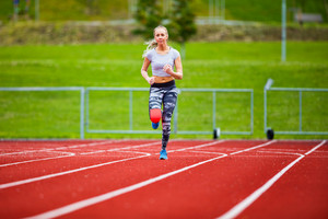 Young Female In Sportswear Running On Sports Tracks