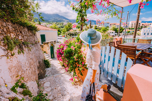 Young female on summer vacation in Greece looking towards wonderful summer day. Cute woman leaving the house and exploring the town. Travel vacation, lifestyle carefree joy and happiness concept