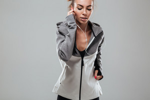 Young female runner in warm clothes running and listening music over gray background