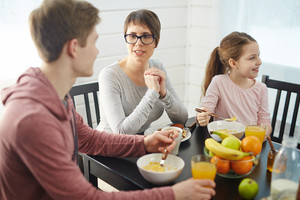 Young female talking to her son by breakfast
