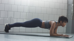 young fit and tone up woman has a rest after fitness workout with plank elements for strenght abs in sunny loft side view. soft camera sake