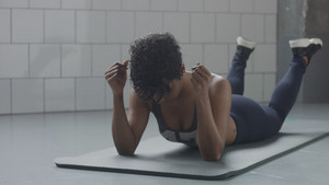 young fit and tone up woman lying relaxed has a rest during her fitness workout with plank elements for strenght abs in sunny loft soft focus.