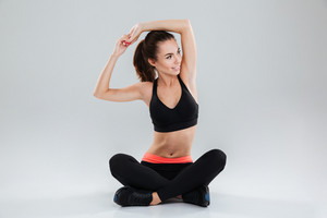 Young fitness woman sitting on the floor in studio and stretching while looking at the camera over gray background