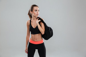 Young fitness woman with bag over gray background