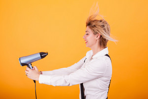Young funny woman blowing her short hair with a hair drayer over yellow background. Cool hairstyle. Haircare.