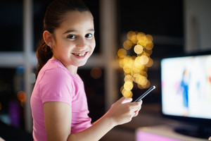 Young girl wearing pajamas, staying awake at night at home. The child is sitting on sofa and looks at camera holding mobile phone. She smiles happy while playing