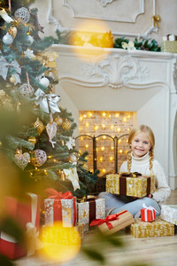 Young girl with gift-box sitting by fireplace and decorated Christmas tree