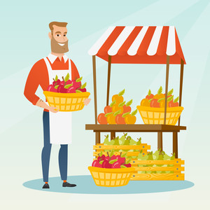Young greengrocer standing near the stall with fruits and vegetables. Greengrocer standing near the market stall. Greengrocer holding basket with fruits. Vector flat design illustration. Square layout