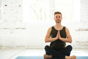 Young guy with eyes closed sitting on a fitness mat and meditating in the gym