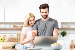 Young happy couple using laptop to look for recipe for their meal
