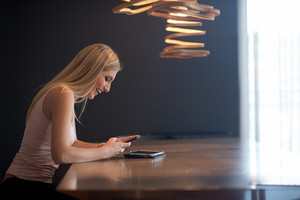 young happy woman sitting at the table and using mobile phone at luxury home