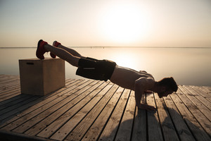 Young healthy man doing push-ups with special equipment on the beach in the morning
