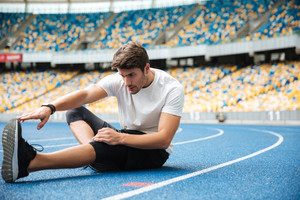 Young healthy sportsman stretching legs while sitting on a racetrack at the stadium