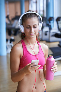 young healthy woman drinking water  in fitness gym while sitting on pilates ball and listening music on headphones from smartphone