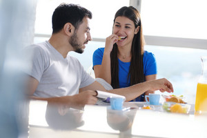 Young hispanic couple having breakfast together on Sunday morning, sitting at table and eating organic food. They smile and eat