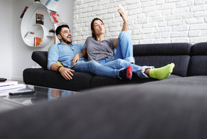 Young hispanic couple laying on couch at home, using a smartphone camera for taking a quick selfie. The boyfriend and girlfriend smile and make facial expressions.