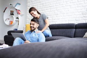 Young hispanic couple sitting on couch at home, using a tablet PC for Internet and social media. The girl is giving a massage to her boyfriend. Copy space