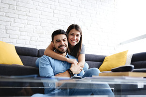 Young hispanic couple sitting on sofa at home, using a tablet PC for Internet and social media. The girl is hugging her boyfriend and smiles at camera. Copy space