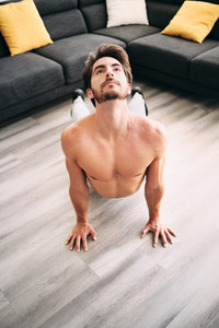 Young hispanic man doing yoga routine for warming up and chakra stimulation. Athlete with bare chest training at home with Sun Salutation Surya Namaskara positions in the morning.