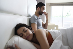 Young hispanic man sneezing for allergy at home. Sick latino man with cold and flu, spreading disease germs and infecting his partner sleeping in the same bed