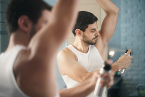 Young hispanic people and male beauty. Confident metrosexual man using spray deodorant on underarm skin, smiling and looking at mirror.
