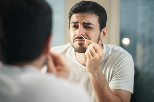 Young hispanic people and male beauty. Metrosexual man feeling pain when trimming nose hair with tweezers