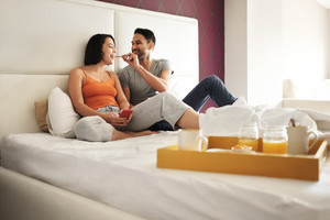 Young latino couple relaxing in bed at home. Hispanic husband and wife eating breakfast in bedroom at morning