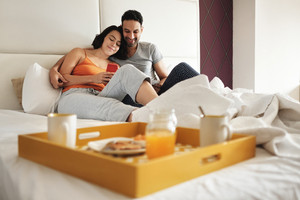 Young latino couple watching funny pictures and video on smartphone in bed at home. Hispanic husband and wife lying in bed and eating breakfast in the morning