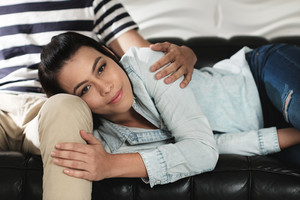 Young latino man and woman holding hands on sofa at home. Happy hispanic couple showing love and romance, with girl smiling and looking at camera