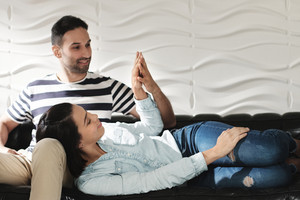 Young latino man and woman holding hands on sofa at home. Happy hispanic couple showing love and romance.