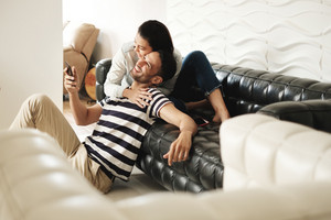 Young latino man and woman messaging with mobile telephones on sofa at home. Happy hispanic couple using cell phones. People using smartphones for social media