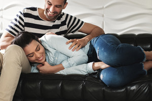 Young latino man tickling his woman on sofa at home. Happy hispanic couple showing love and romance.