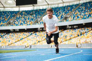 Young male athlete running on a racetrack at the stadium