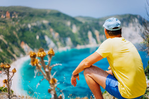 Young male enjoys Petani beach on Kefalonia. Highly excited picturesque panorama of emerald blue lagoon bay of Mediterranean sea. Greece