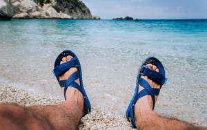 Young male feet wear blue flip-flop sandal sunbathing on pebble beach in front of blue sea water and rocks in background on horizon