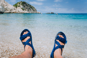 Young male feets wear blue flip-flop sandal sunbathing on pebble beach in front of blue sea water and rocks in background on horizon