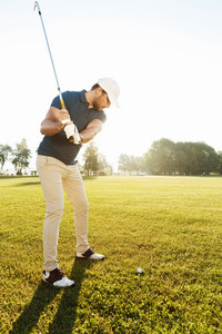 Young male golfer hitting ball with a club playing at the green course