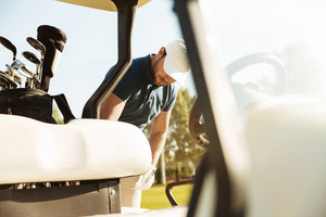 Young male golfer standing at the golf cart outdoors