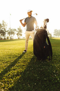 Young male golfer standing on a green field with a golf bag
