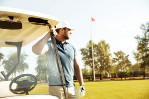Young male golfer standing while leaning on a golf cart