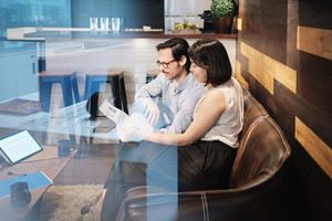 Young male manager working in modern office cafeteria and meeting female colleague. Busy business man and woman at work in corporate coworking space lounge. Team of businessman and businesswoman